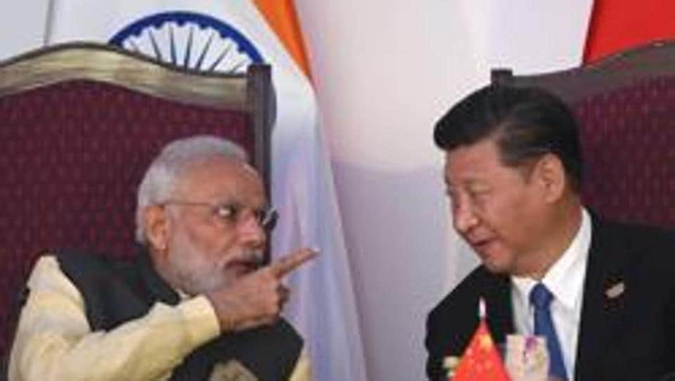 Prime Minister Narendra Modi gestures while talking with China's President Xi Jinping during the BRICS leaders' meeting with the BRICS Business Council in Goa on October 16, 2016.