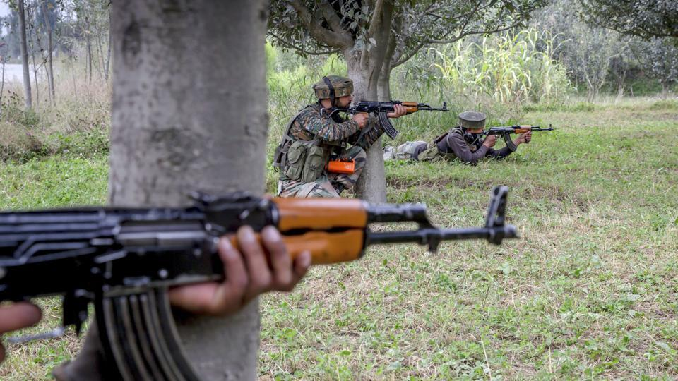 Indian army soldiers take position inside an apple orchard near the site of gunbattle in Pulwama on August 26.