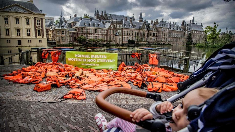 A baby in a stroller passes by life jackets displayed by International anti-poverty organisation OXFAM NOVIB in front of the Dutch Parliament at the Binnenhof in The Hague. The jackets serve as a visual reminder to the Dutch government of the suffering and risks hundreds of thousands of refugees have endured.  (AFP)