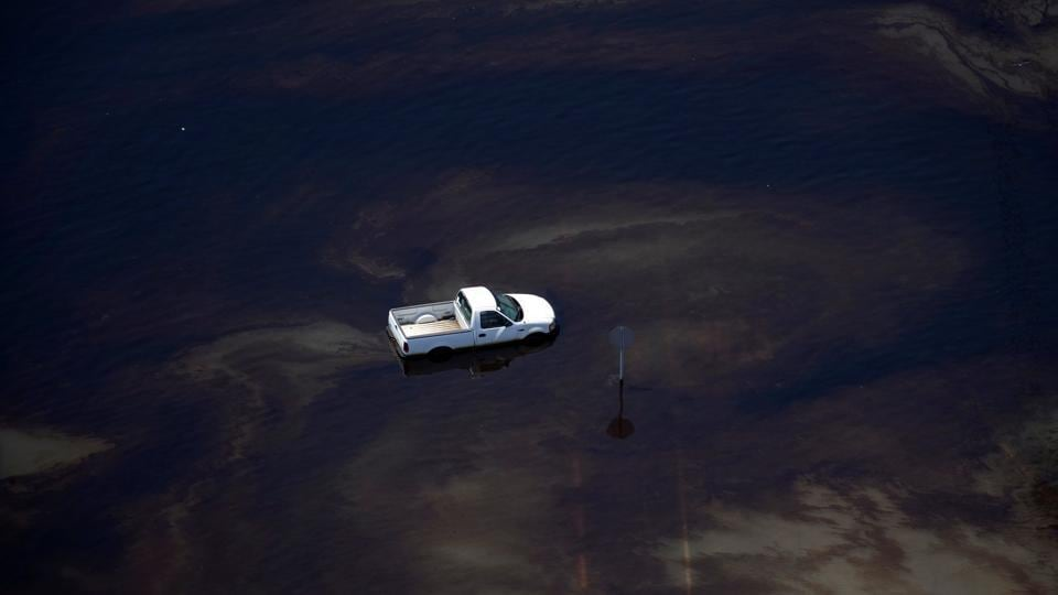 A vehicle sits amid leaked fuel mixed in with flood waters caused by Tropical Storm Harvey in the parking lot of Motiva Enterprises LLC in Port Arthur, Texas, U.S.  (Adrees Latif  / REUTERS)