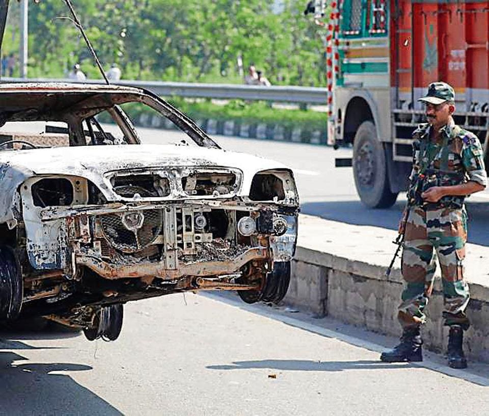 A soldier looks at a car damaged in arson, a day after the August 25 violence in Panchkula.