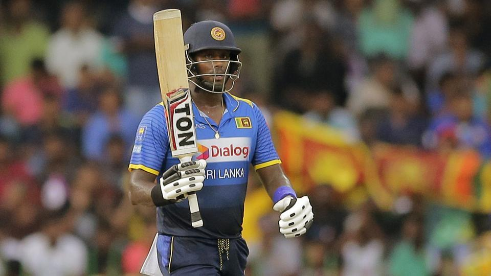 Sri Lanka's Angelo Mathews raises his bat to celebrate scoring fifty runs during their fifth and last one-day international cricket match against India in Colombo on Sunday.