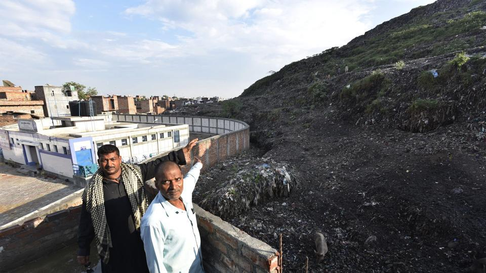 Residents of Bhalswa pointing out at the landfill near their houses.