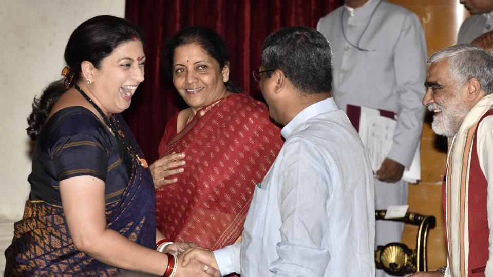 Smriti Irani greets Dharmendra Pradhan as Nirmala Sitharaman looks on during the swearing-in ceremony at the Rashtrapati Bhawan in New Delhi on September 3, 2017. PMNarendra Modi rejigged his Council of ministers for a third time since he became prime minister in 2014.