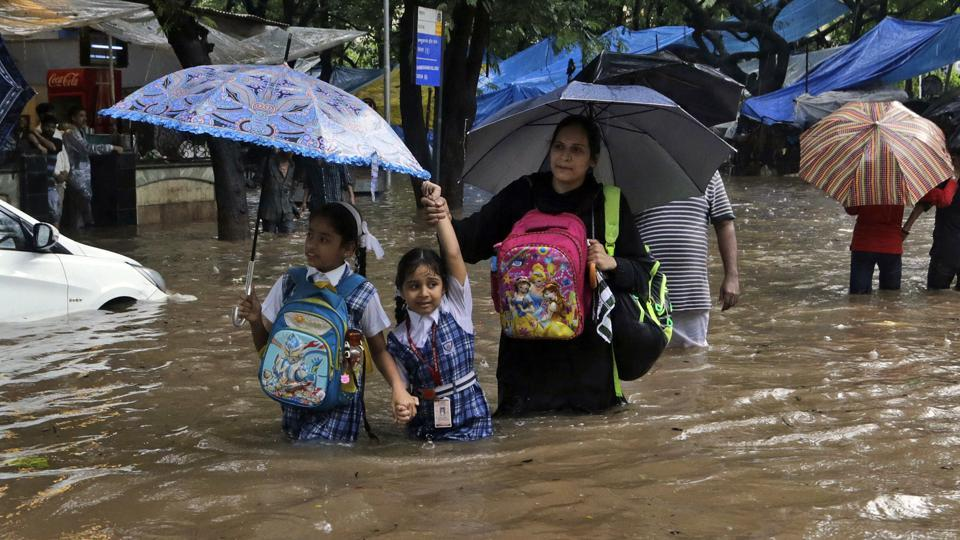 Schoolchildren walk through a waterlogged street in Mumbai. Unicef said almost 16 million children and their families are in urgent need of life-saving support.