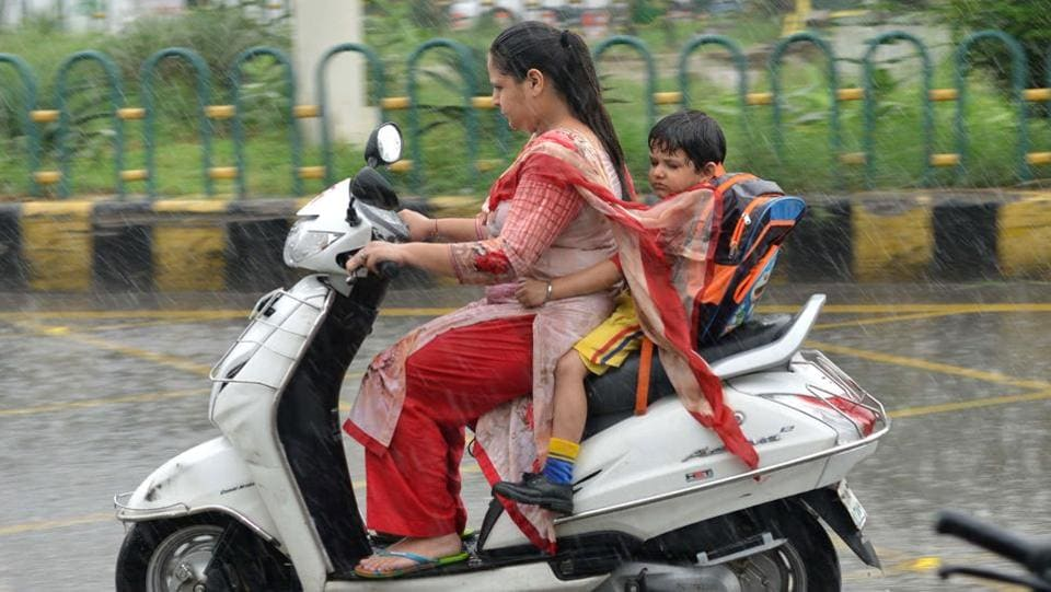 An Indian woman rides a bike with a boy during heavy rains in Amritsar. (NARINDER NANU / AFP)