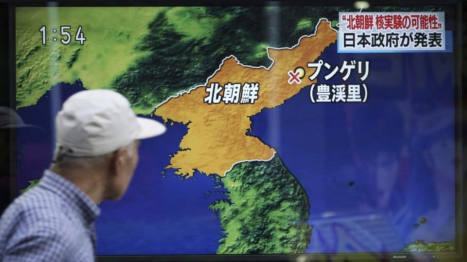 A man in Tokyo walks past a TV news screen reporting North Korea's a possible nuclear test on Sunday.