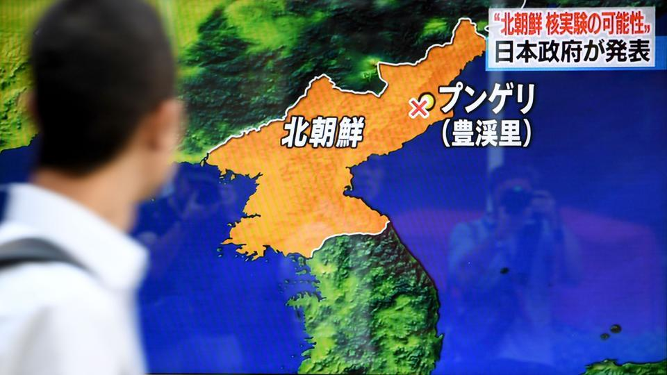 A pedestrian walk past a television screen broadcasting a news programme on a North Korean nuclear test, in Tokyo on September 3, 2017.