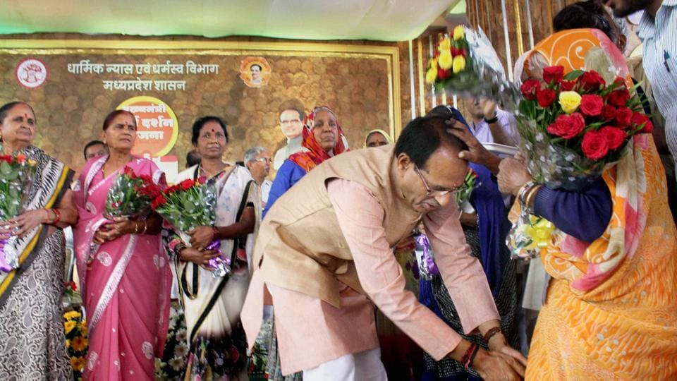 Madhya Pradesh chief minister Shivraj Singh Chouhan welcomes and seeks blessings of elderly pilgrims during a programme organised on the completion of five years of 'Mukhyamantri Teerth Darshan Yojana' in Bhopal on Sunday.