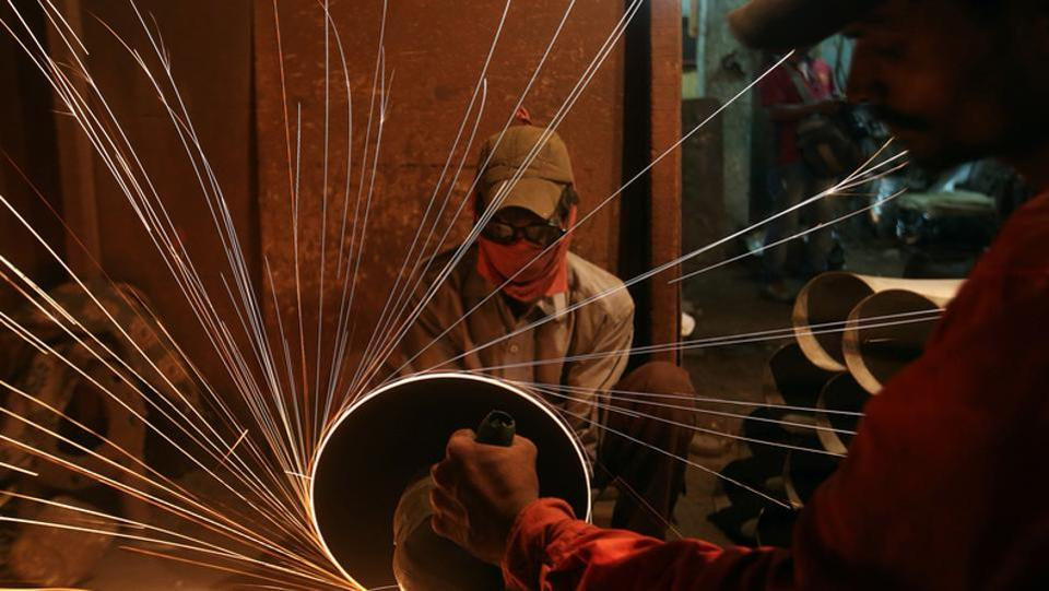 A worker cuts metal inside a workshop manufacturing metal pipes in Mumbai. (Shailesh Andrade / REUTERS)