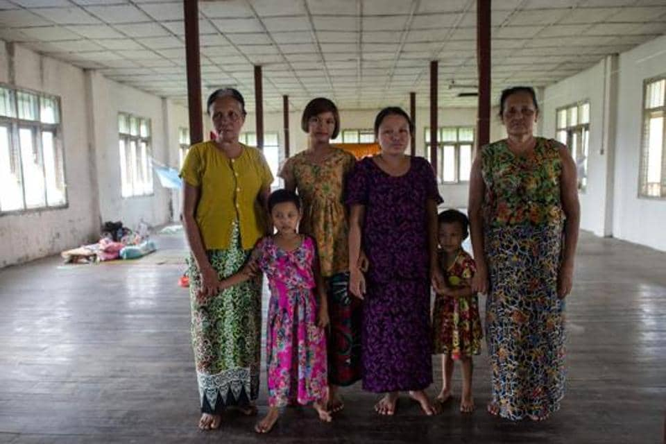 In this photograph taken on August 30, 2017, Daw Bu (L), 64, who fled from Maungdaw, is seen with her sister (R), daughter-in-law (C) and three grandchildren at an internally displaced persons (IDP) camp in Sittwe.