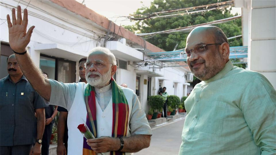 Prime Minister Narendra Modi waves at supporters as BJP President Amit Shah looks on, prior to a meeting with chief ministers of BJP-ruled states in New Delhi.