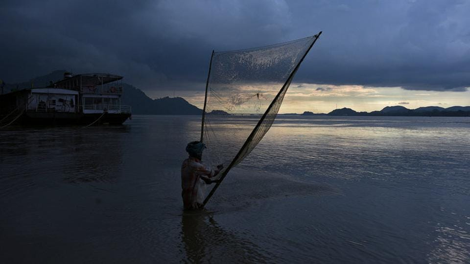 A man catches fish  on the banks of the Brahmaputra river in Guwahati. (Anuwar Hazarika / REUTERS)