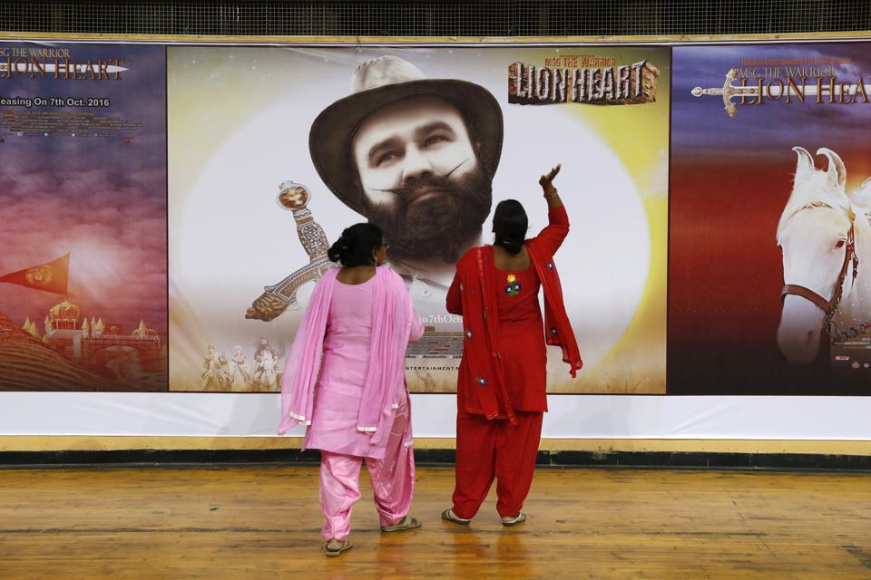 Devotees of Gurmeet Singh Ram Rahim Insan, stand near a poster of his film