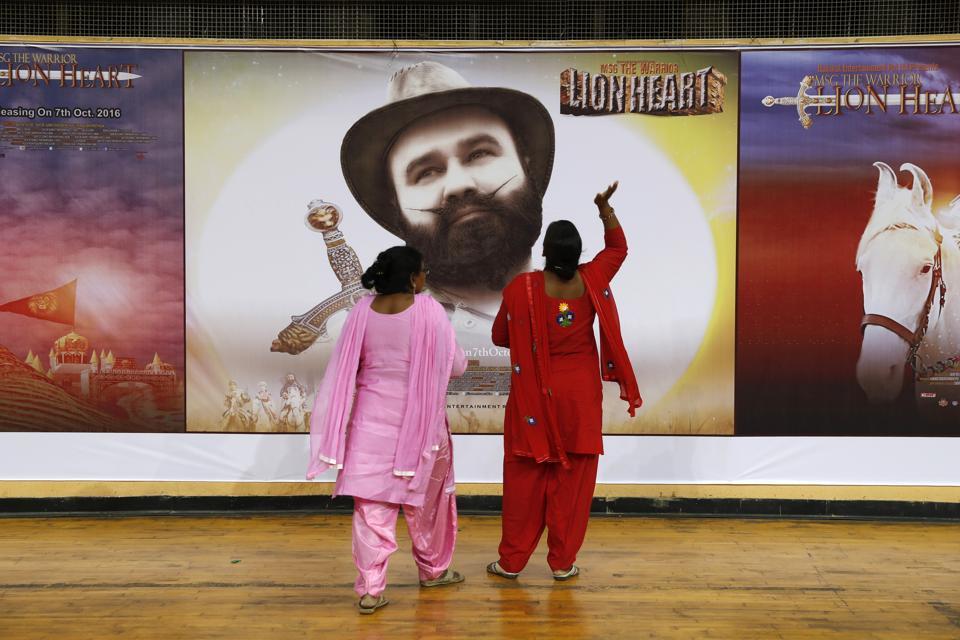 Devotees of Gurmeet Singh Ram Rahim Insan, stand near a poster of his film
