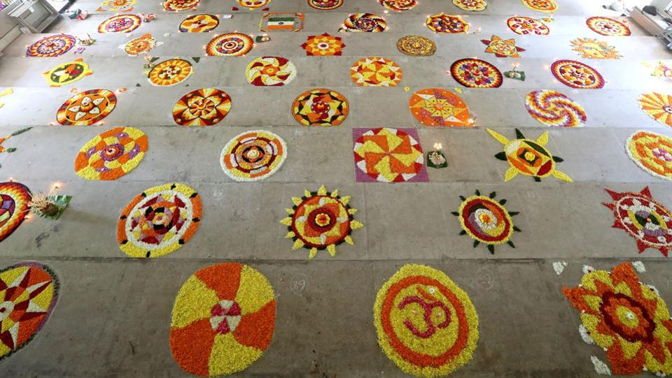 Women create floral patterns  as part of Pookalam competitions. Being a harvest festival and a family affair, on Thiruonam it's mostly a family affair with families confined to their homes and attending to guests serving traditional Onam Sadhhya- a feast involving traditional delicacies cooked with vegetables and spices from Kerala and payasam- sweet dish. (Vivek Nair  / HT Photo)