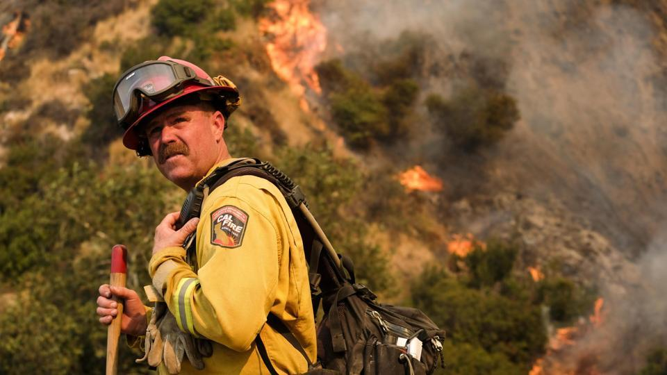 A crew member with the California Department of Forestry and Fire Protection battles a brushfire on the hillside in Burbank.