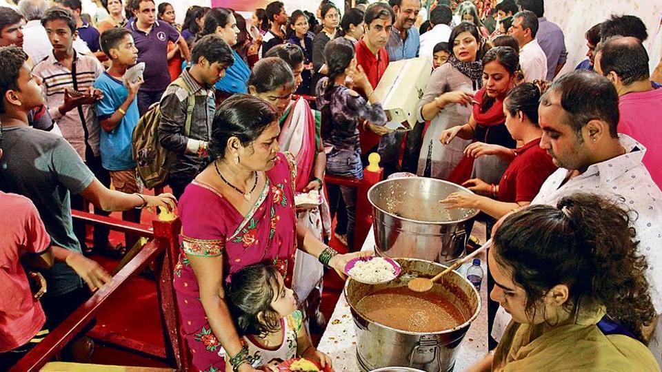 Volunteers at Chemburcha Raja serve food to devotees at the pandal.