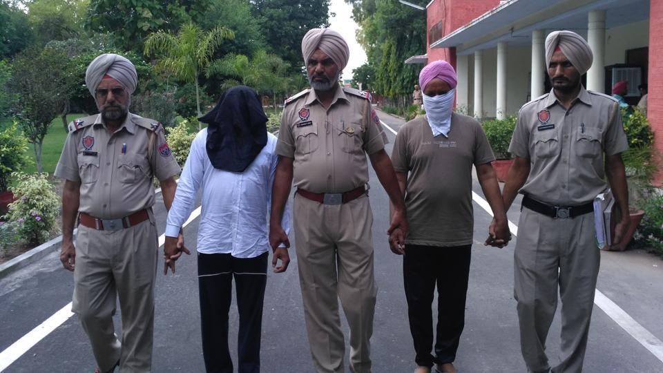 Duni Chand and Ranjit Singh (faced covered) in police custody.
