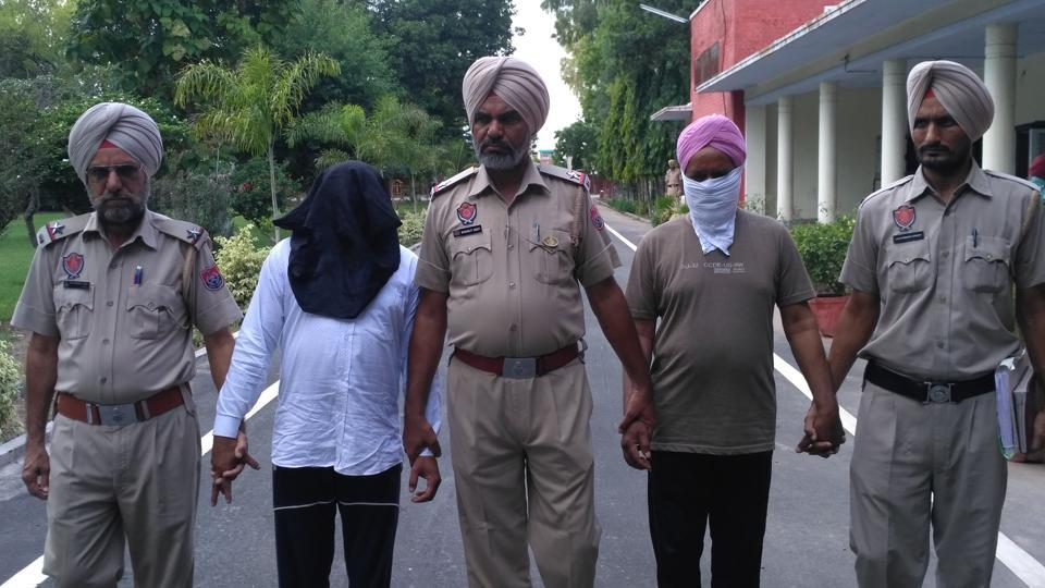 Dera followers Duni Chand and Ranjit Singh (with faces covered) in police custody in Sangrur on Monday.