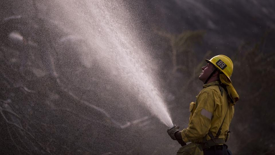 A smattering of rain and easing temperatures helped more than 1,000 firefighters battling the largest wildfire in Los Angeles history gain the upper hand on the blaze on Sunday but officials warned that danger remains.Shifting winds could cause burning embers to spread the fire once more through the rugged northern edge of Los Angeles, said Garcetti. (David McNew / AFP)