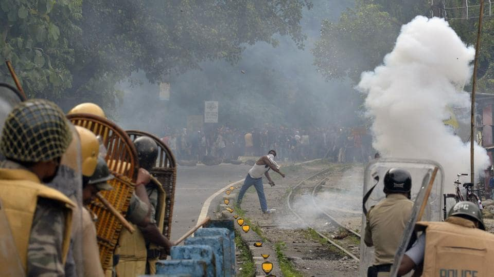 This file photo taken on July 29, 2017, shows a supporter of a separate Gorkhaland state throwing a projectile at police during an indefinite strike at Sukna village in Darjeeling.