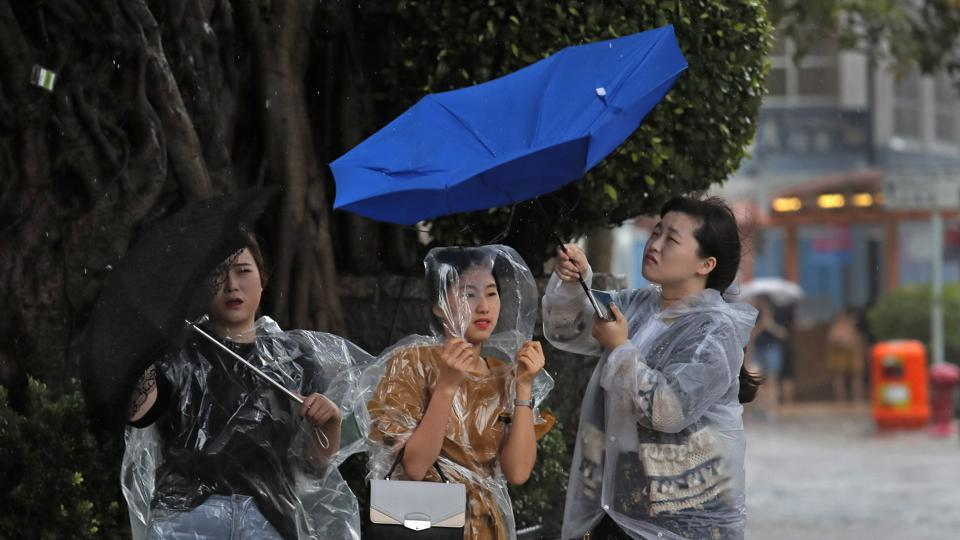 In this August 27, 2017, file photo, people hold umbrellas against the strong wind caused by tropical storm Pakhar near the waterfront of Victoria Harbor in Hong Kong.