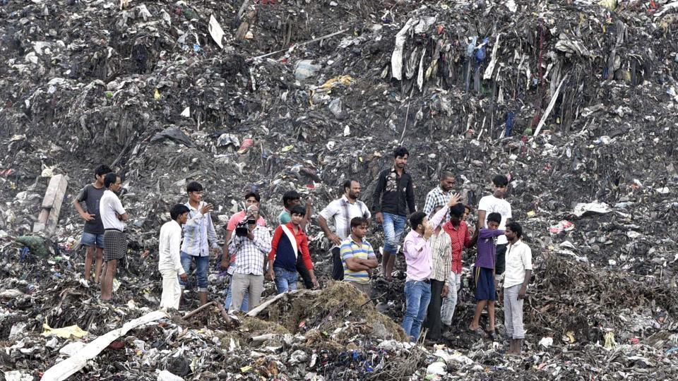 People stand atop a garbage landfill after part of it collapsed in Ghazipur area on Friday.