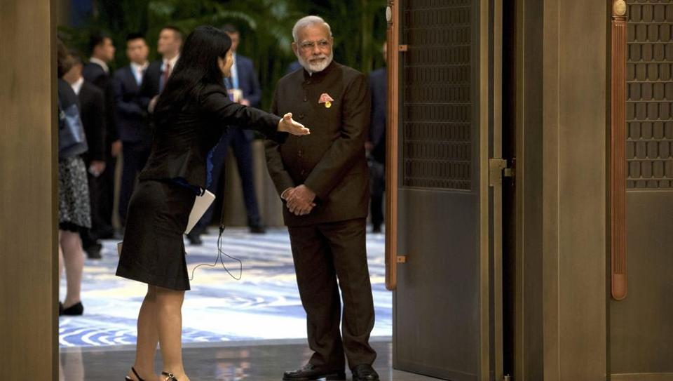 A staff member gestures to Indian Prime Minister Narendra Modi as he waits to enter a reception hall during the BRICS Summit in southeastern China's Fujian province on September 4, 2017.