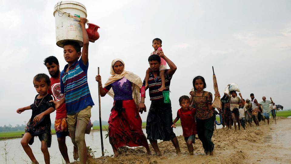 Rohingya refugees walk on the muddy path after crossing the Bangladesh-Myanmar border in Teknaf, Bangladesh, September 3, 2017.