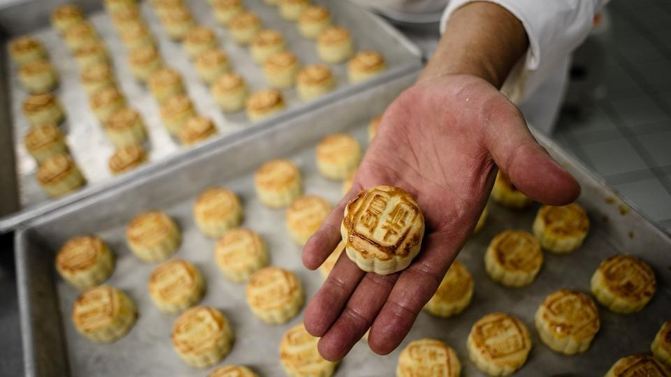 "Chef Yip Wing-wah displays his freshly oven-baked signature ""spring moon mini egg custard mooncakes"" at Hong Kong's famous colonial era Peninsula Hotel."