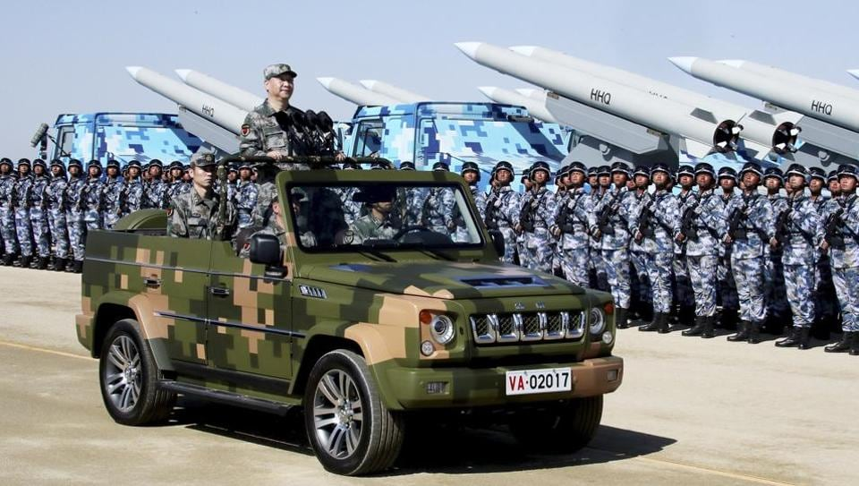 Chinese President Xi Jinping stands on a military jeep as he inspects troops of the People's Liberation Army during a military parade in July 2017