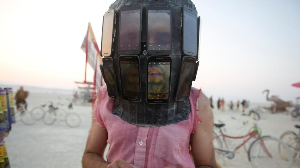 Derek Schoonmaker walks on the playa with his helmet made of android phones as an experimental project. (Jim Urquhart / REUTERS)