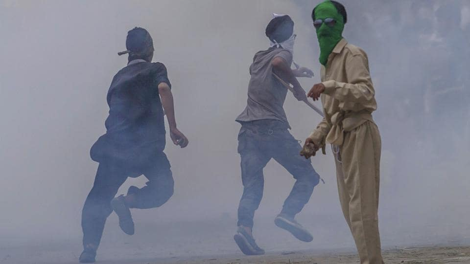 A Kashmiri protester holds a rock in his hand as others run for cover amid tear gas smoke during a protest outside Eidgha, a prayer ground, in Srinagar.