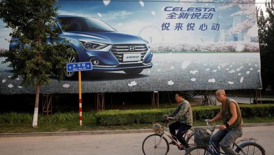 Men cycle past an advertising billboard for Hyundai cars opposite the plant of Hyundai Motor Co in Beijing. (REUTERS)