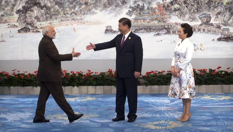Indian Prime Minister Narendra Modi reaches to shake hands with Chinese President Xi Jinping as his wife Peng Liyuan watches during the BRICS Summit in China's Fujian Province