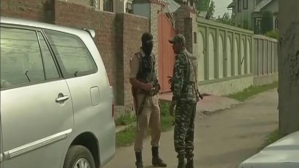 Policemen stand guard during a NIA raid inSrinagar on September 6, 2017.