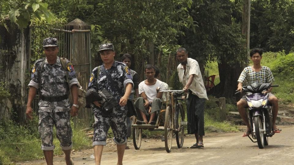 Myanmar Border Guard Police walk ahead of a Rohingya trishaw driver and passenger along the main road of Buthidaung, northern Rakhine state of Myanmar, on September 6, 2017. Myanmar leader Aung San Suu Kyi's top security adviser sought to counter the storm of criticism the government is facing from around the world over alleged army abuses against ethnic minority Rohingya, asserting that security forces were acting with restraint in pursuing