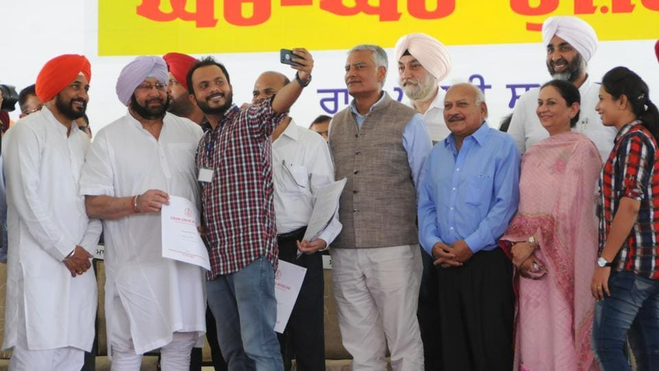 A man who was received a job letter takes a selfie with Punjab CM Capt Amarinder Singh and technical education minister Charanjit Singh Channi in Mohali on Tuesday.