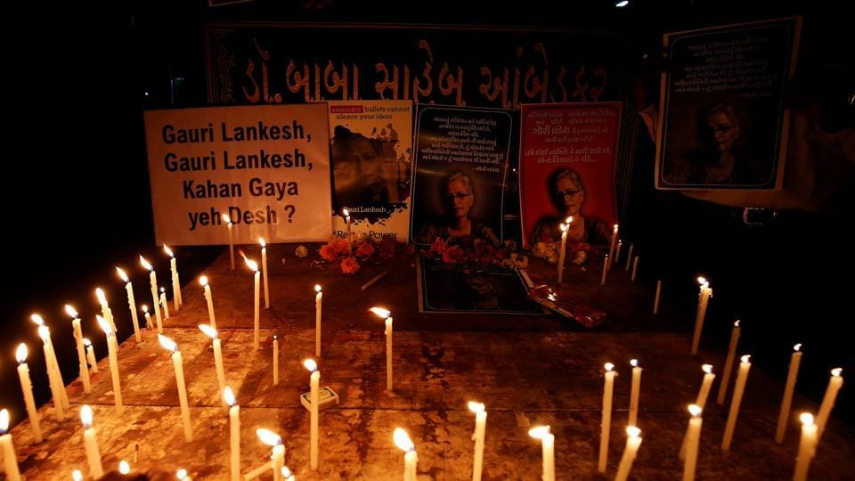Candles are kept in front of photos of Gauri Lankesh, who according to police was shot dead outside her home on Tuesday.