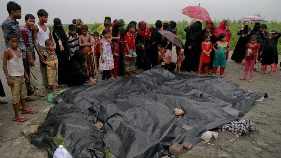 Bangladeshi villagers gather around bodies of Rohingya women and children at Shah Porir Deep, in Teknak, Bangladesh, after a capsizing accident. Refugees have been fleeing, aided by smugglers charging about 10,000 Myanmar kyat (approx ₹500) for each person in the family to be ferried across the rivers adjoining Bangladesh and Myanmar in rickety wooden boats. (Suvra Kanti Das / AP)