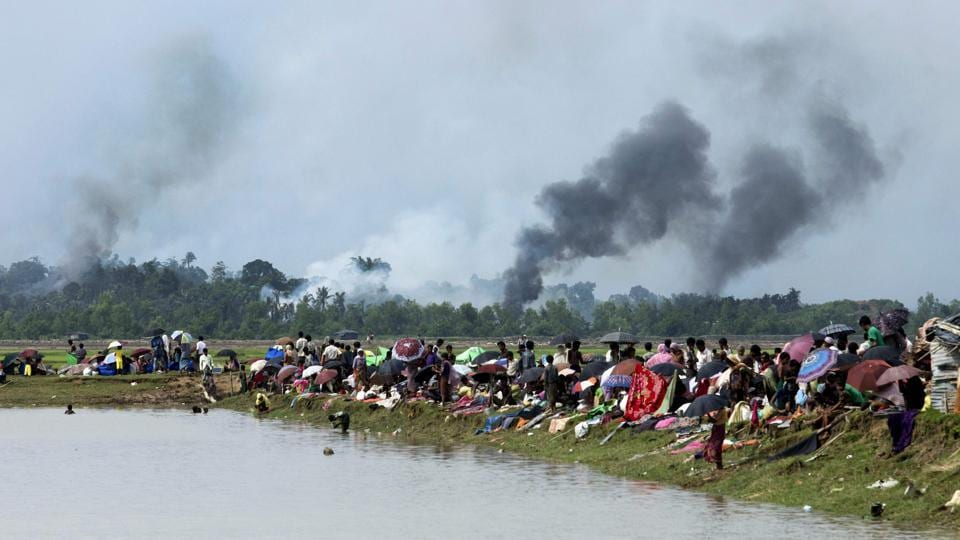 Smoke billows above what is reported to be a burning village in Myanmar's Rakhine state as members of the Rohingya Muslim minority take shelter in a no-man's land between Bangladesh and Myanmar in Ukhiya on September 4, 2017. Almost 15,000 Rohingya refugees are estimated to cross the Naf river into Bangladesh each day this week, scrambling for shelter in overcrowded camps and makeshift settlements. (K. M. Asad / AFP)