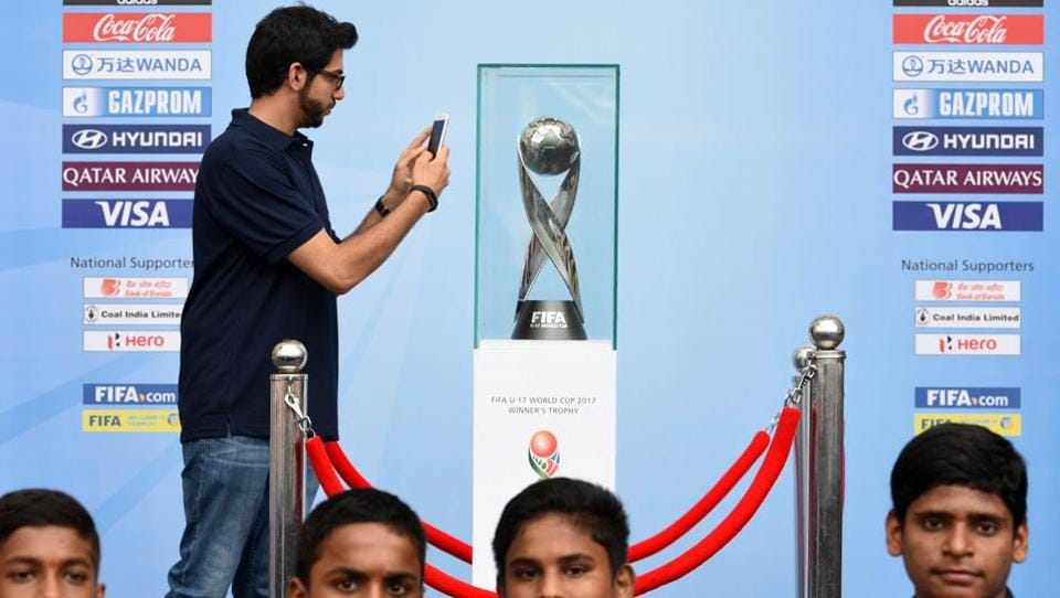 Aditiya Thackeray clicks a picture of the FIFA U-17 Wordl Cup winners trophy. (Hindustan Times)