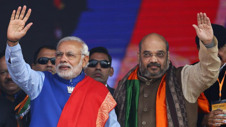 Indian Prime Minister Narendra Modi (L) and Amit Shah, the president of India's ruling Bharatiya Janata Party (BJP), wave to their supporters during a campaign rally ahead of state assembly elections, at Ramlila ground in New Delhi.