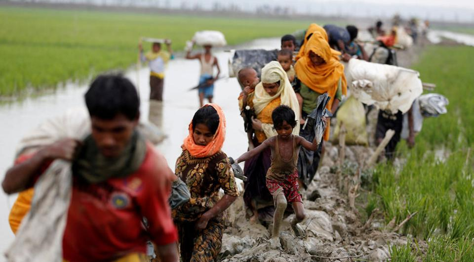 Rohingya refugees walk on a muddy path after crossing the Bangladesh-Myanmar border in Teknaf in Bangladesh.