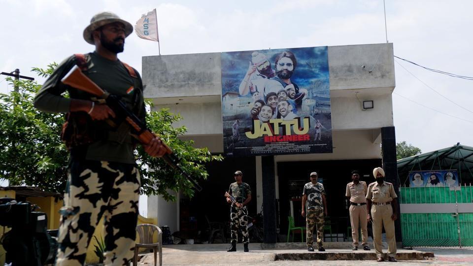 Cops standing guard before huge posters of Gurmeet Ram Rahim's latest movie 'Jattu Engineer' near the naam charcha ghar at Patran in Patiala.