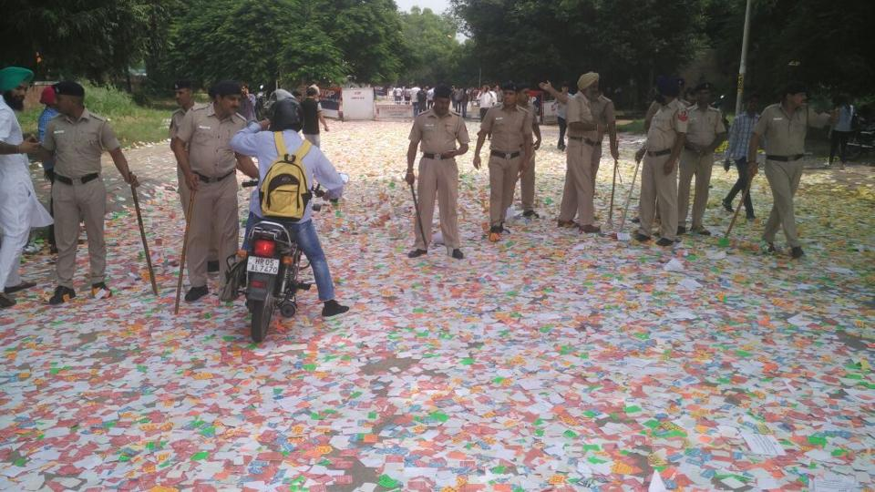 Police security personnel stand upon a sea of stickers outside DAV College, Sector 10, on Thursday.   (Karun Sharma/HT)