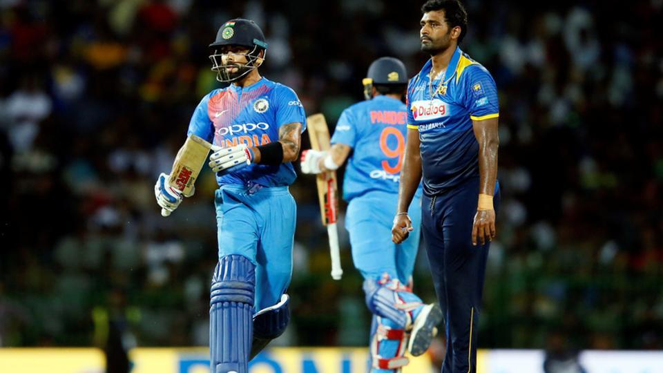 Virat Kohli runs between wickets next to Sri Lanka's Thisara Perera during the one-off T20 in Colombo on Wednesday. India won by seven wickets.