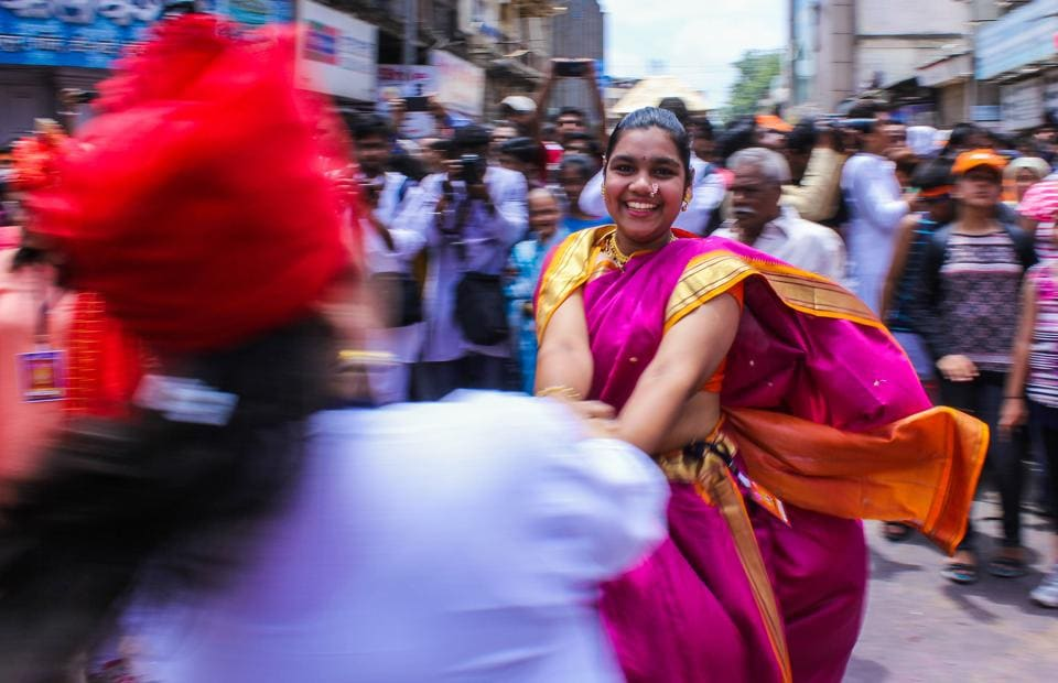 A woman dressed in traditional Maharashtrian attire plays folk dance fugdi during Ganesh visarjan procession in Pune on Tuesday. (Sanket Wankhade/HT PHOTO)