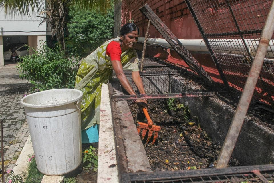 A society worker mixes the wet waste collected from the houses in the society to cook up compost in Pune.